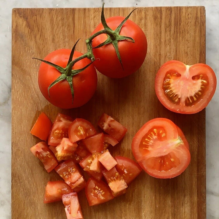 two whole red tomatoes, 2 halved red tomatoes and chopped tomatoes on a wooden chopping board