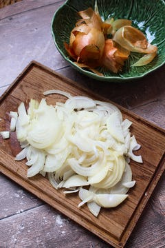 finely chopped onion on a wooden chopping board