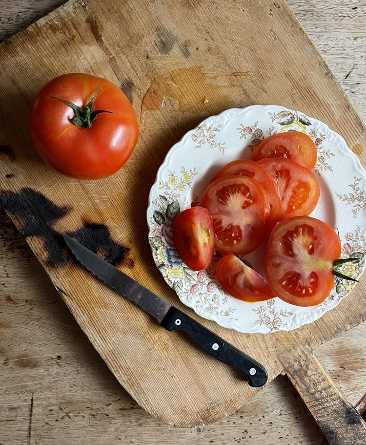 plate of sliced tomato, half a tomato on the side with knife and a whole tomato on top of a wooden board