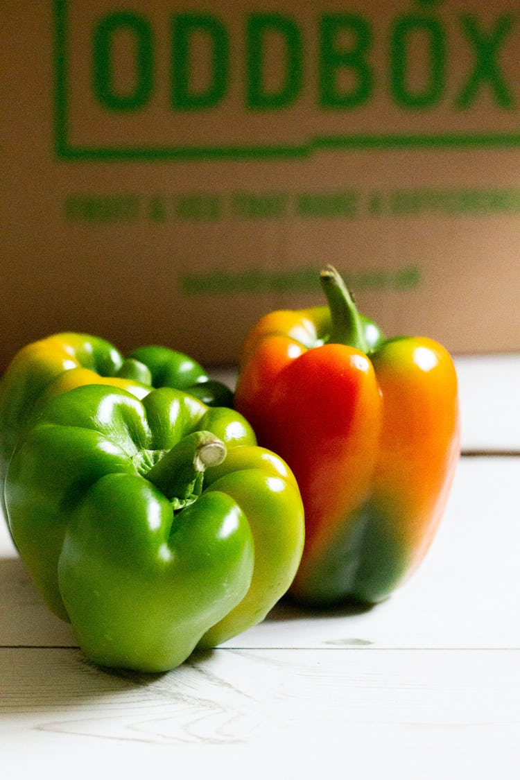 green bell pepper , one green bell pepper turning  and oddbox logo in the back