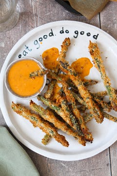 A plate of asparagus fries with a bowl of dipping sauce.