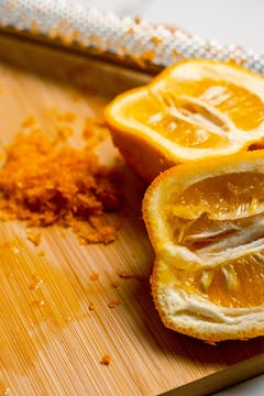 Seville oranges cut in half on a chopping board with grated zest next to them.