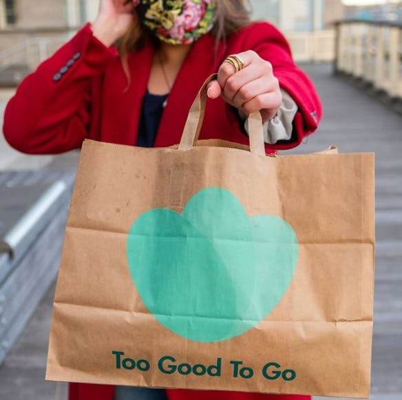 A woman in a face mask holding a paper Too Good to Go Bag