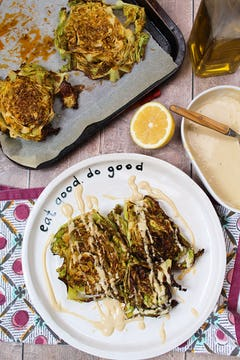2 slices of roasted savoy cabbage steak drizzled with tahini dressing on white plate.half a lemon on the side and tahini dressing on a serving bowl. 2 more roasted savoy cabbage steaks on a baking tray