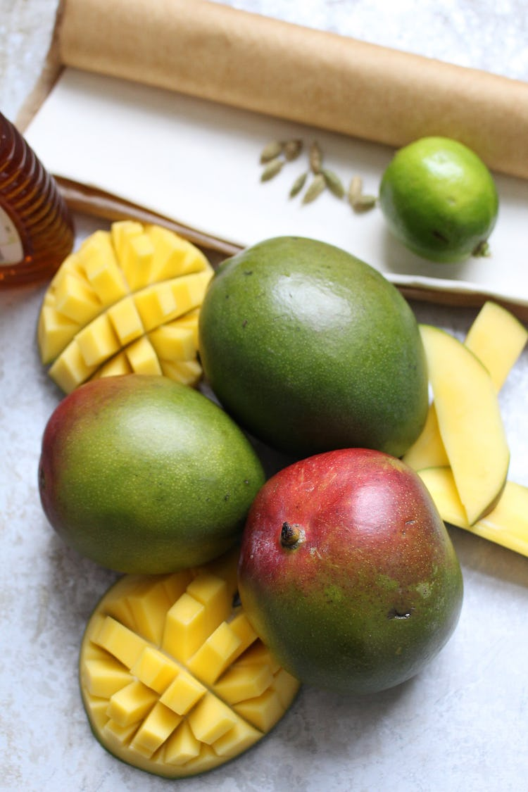 3 whole mangoes and 2 slice of mango on the skin cut into square shaped