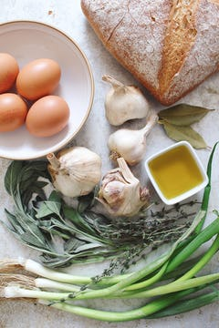 bunch of spring onion, thyme, 4 whole garlic, 2 bay leaves, little bowl of oil, 4 whole eggs on a bowl and bread