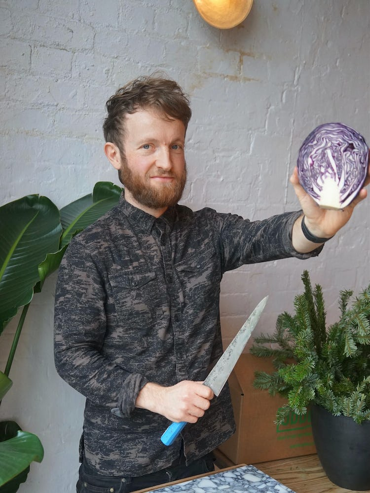 Douglas McMaster holding a purple cabbage and a knife, about to prep it.