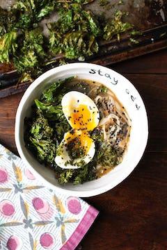 served kale noodle broth with egg and black sesame seeds