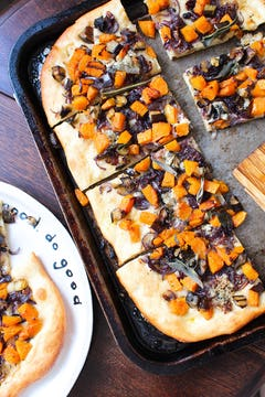 Roasted squash and aubergine pizza with caramelised onions on a baking tray