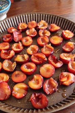 Plums drizzled with syrup on baking tray