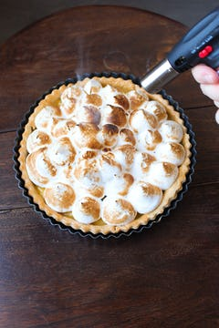 blow torch is being used to cook the meringue