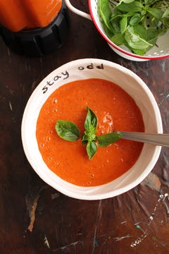 served roasted bell pepper gazpacho on bowl with basil leaves