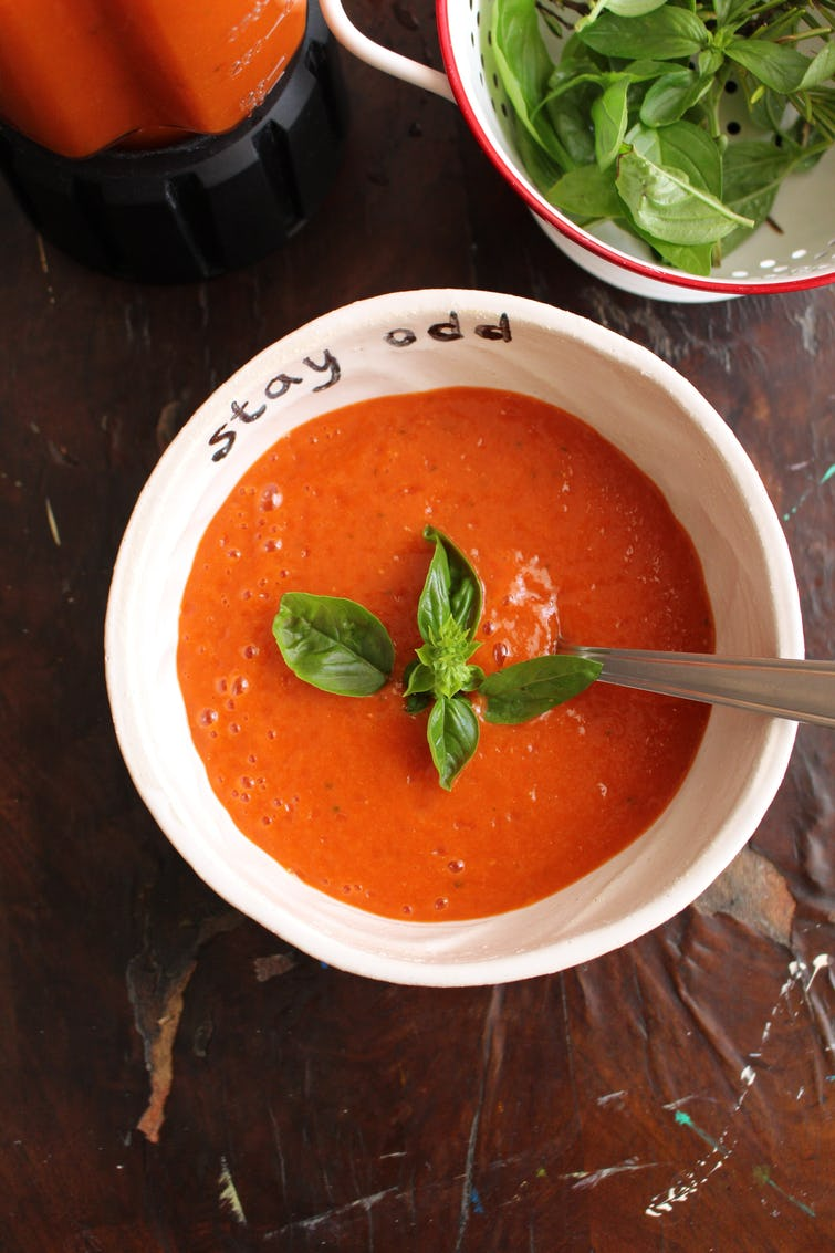 Roasted bell paper gazpacho served in bowl, garnished with basil