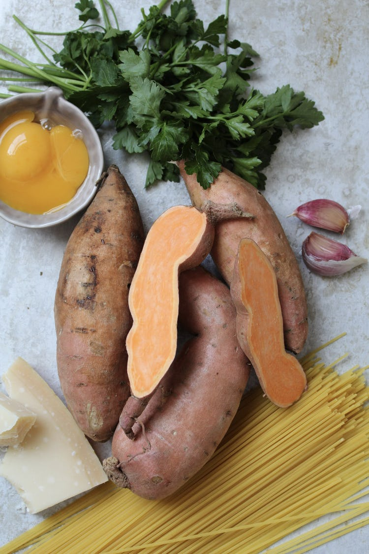 A pile of sweet potatoes with dried spaghetti, egg yolks, coriander, and 2 cloves of garlic.