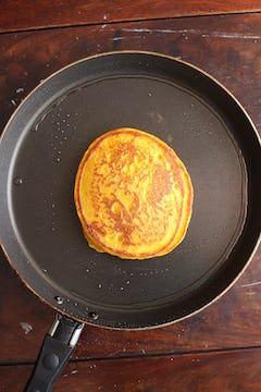 a singular pancake cooked on a frying pan