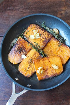 Butternut squash, thyme and garlic cooking in frying pan