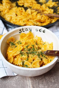 creamy carrot pasta served in bowl with parsley