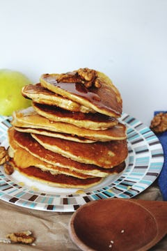stack of pancakes drizzled with syrup and walnut