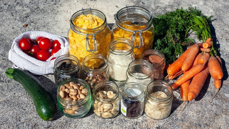 Jars of different nuts and dried fruits, carrots, one courgette and cherry tomatoes on the side