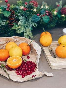 Oranges wrapped in baking paper with cranberries and herbs. There's a chopping board with 4 more oranges on top; a Christmas table wreath is visible beyond the oranges.