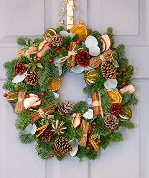 A foraged Christmas wreath with cinnamon sticks, pinecones, dried orange and apple slices, and cranberries.