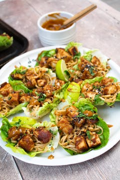 A plate of peanut butter tofu lettuce wraps with a bowl of sauce.