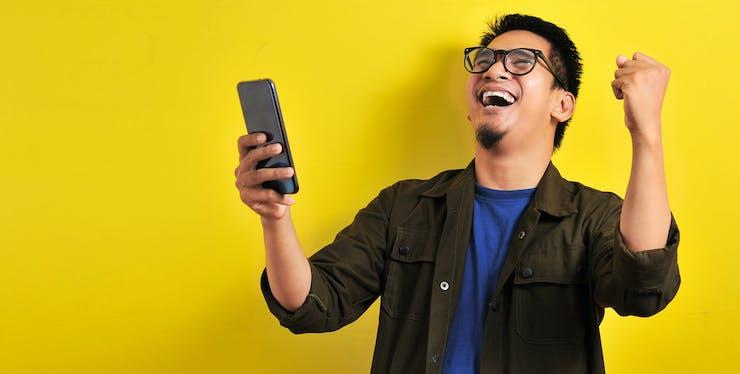 homem comemorando enquanto segura celular