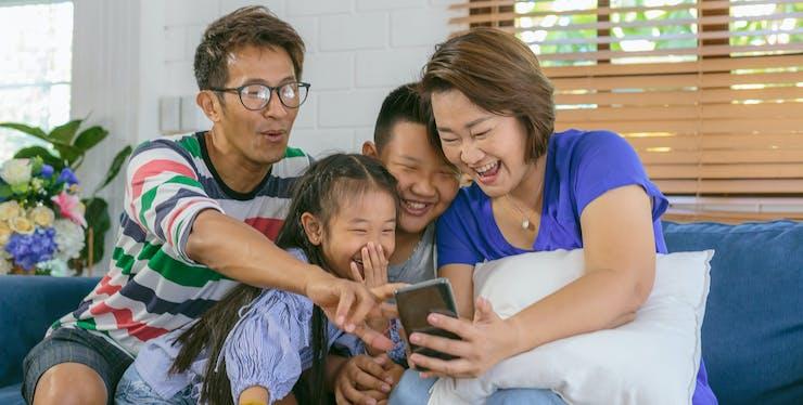 família sorrindo enquanto olham para celular