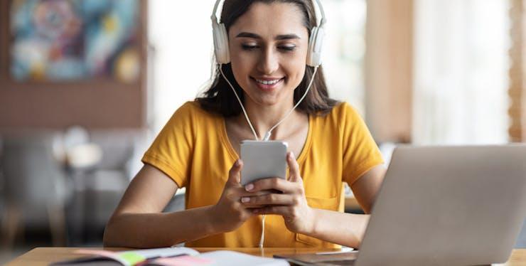 Menina mexendo no celular e usando headphone