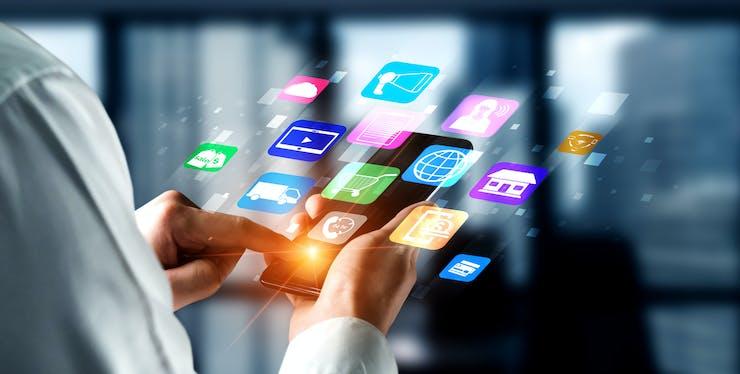 mão segurando celular com vários símbolos de aplicativos projetados fora da tela