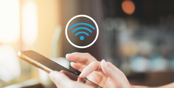mãos segurando celular e ícone de sinal de internet WiFi em cima do telefone