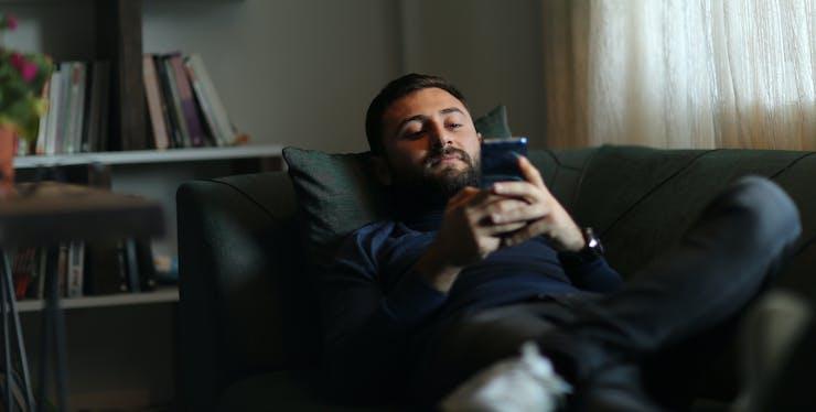 homem deitado lendo no celular