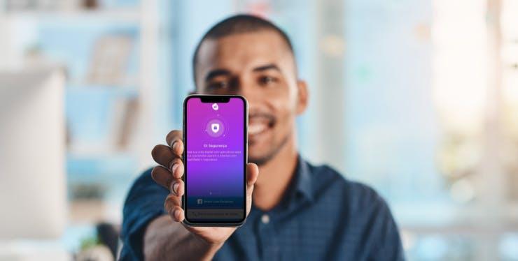 homem segurando celular com tela do Oi Segurança