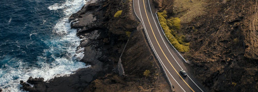 Photo of road along a rocky shoreline on O'ahu.