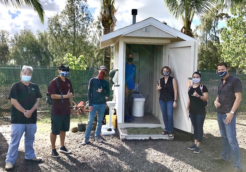 Photo of group of people standing in front of an outdoor Cinderella Incineration Toilet