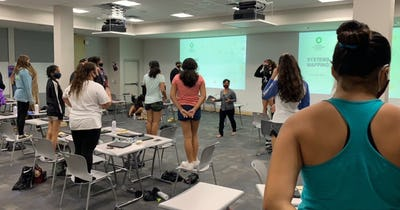 Photo of Girls in a conference room doing a group activity while standing on top of chairs.