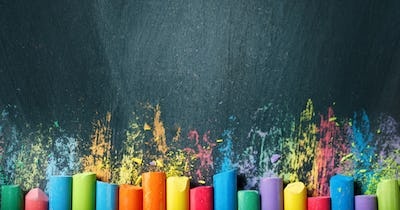 Photo of different colored chalk pieces on a chalkboard background