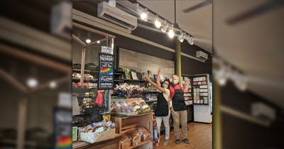 Photo of store employees showcasing new energy-efficient light fixtures