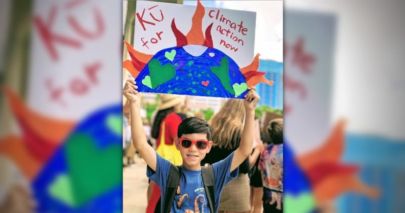 Photo of a child at a rally holding a sign in support of climate action