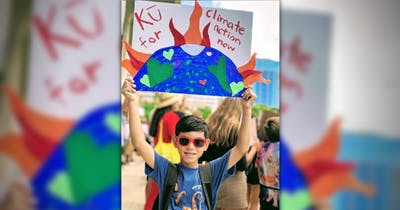 Photo of a child holding sign at a rally in support of climate action