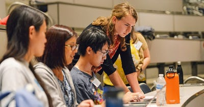 Photo of students developing an app on a laptop computer