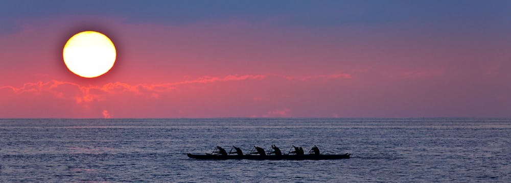 Photo of canoe paddlers on the ocean
