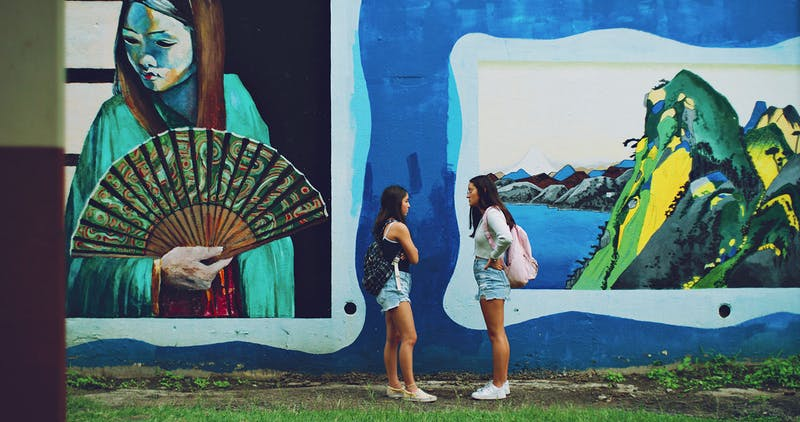 Photo of two students talking to each other in front of a mural
