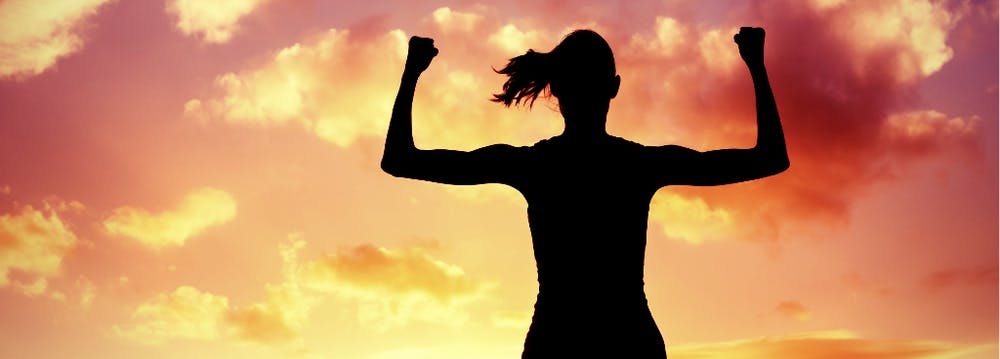 Photo of a silhouetted woman flexing her arms and showing strengths