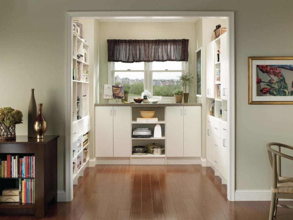 A white kitchen pantry with custom organizers.