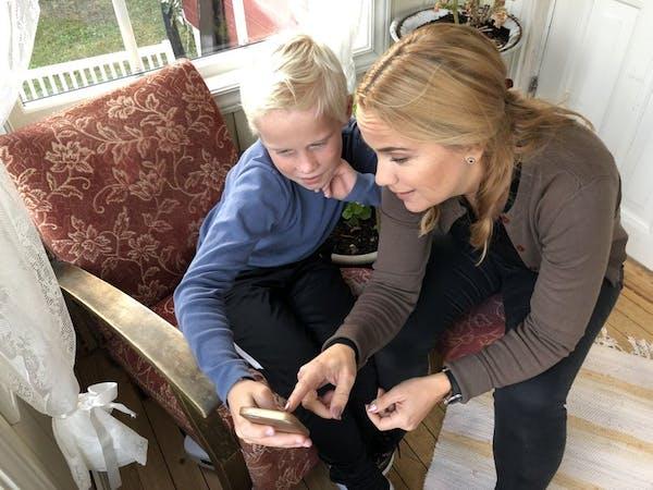 Mor og sønn sitter og ser på sønnens mobiltelefon.