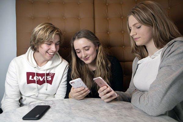 3 ungdommer sitter rundt et bord og ser på mobiltelefonene sine.