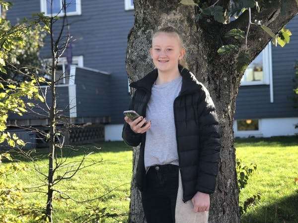 Ung jente står med mobiltelefon i hånden.