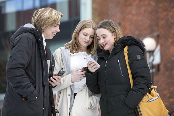 3 ungdommer står og ser på mobiltelefonene sine.