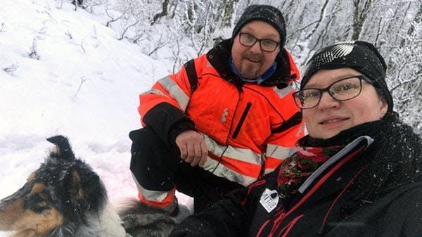 Mann, kone og hund på tur i skogen om vinteren.